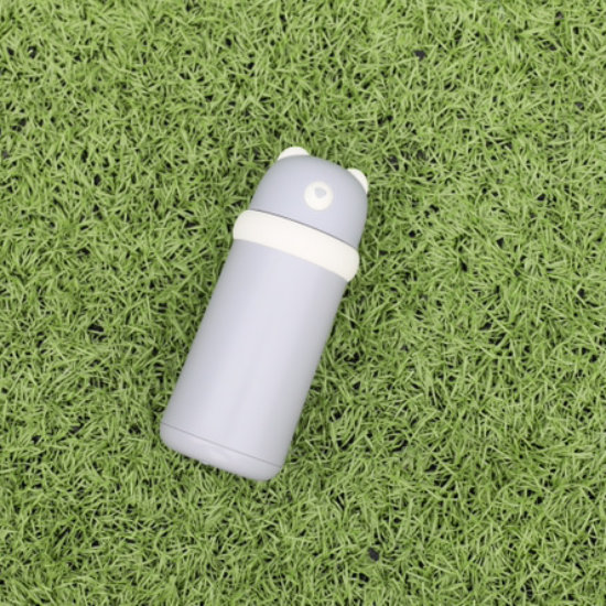 BeddyBear Double Walled Insulation Bottle Grey Color, laid down on grass