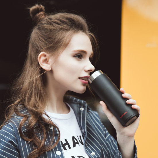 A Female Model drinking from BeddyBear Vacuum Flask Mini Series Black Color
