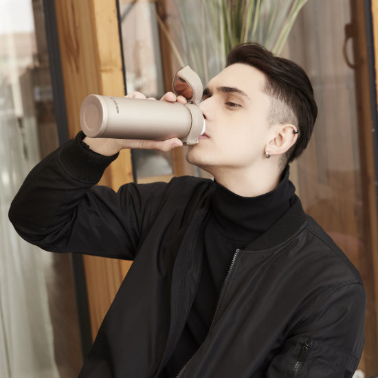 A Male Model drinking from BeddyBear Vacuum Flask Radiant Gold