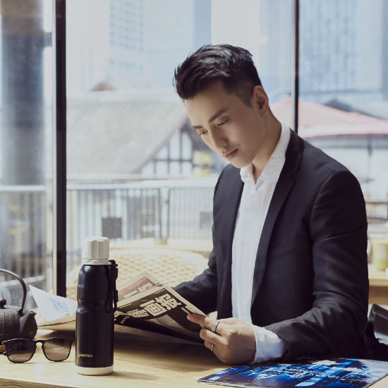 A Male Model reading newspaper with BeddyBear Sports Vacuum Bottle Black Color in front of him